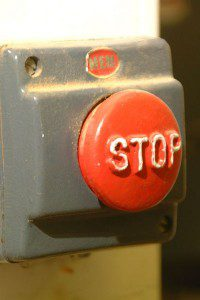"""Red """"stop"""" button on a grey box."""