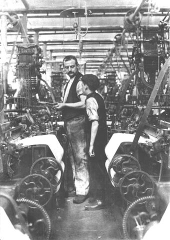 Black and white image of a man and a boy standing in a narrow aisle between ranks of machines in a UK textile mill in 1903. Source: UK National Archives.