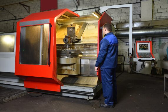 Worker standing in front of a CNC milling machine with the guard open.